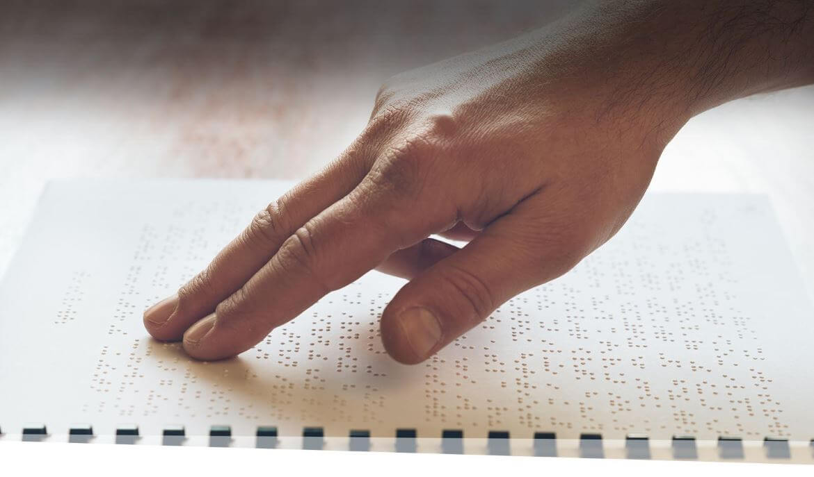 Visually impaired elderly person learning to read by touch using Braille.